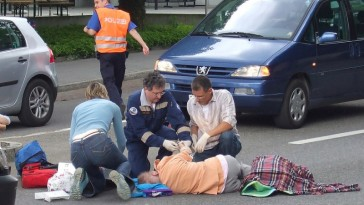Photo of emergency workers helping a woman hit by a car