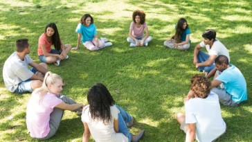 Photo of a young people sitting in a circle on the lawn